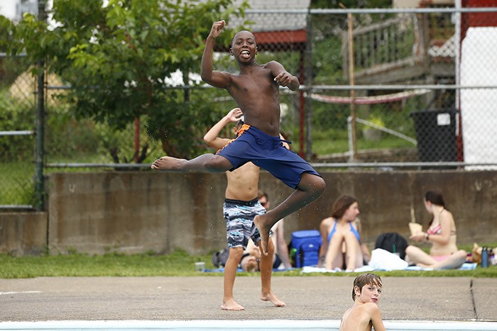 Jordan, 11, jumps into the Bloomfield pool while posing for the camera - CP PHOTO: JARED WICKERHAM