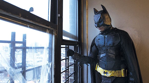 """""""The Dark Knight,"""" in a suit made of cardboard and yoga mats, surveys Gotham."""