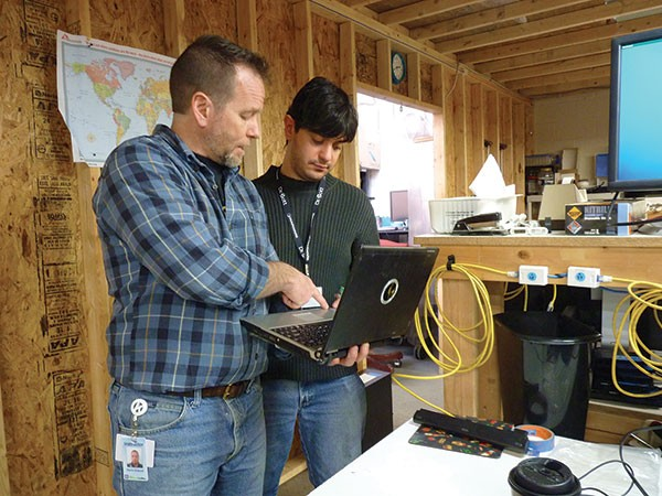 Kevin Driscoll, of Computer Reach, and volunteer Pietro Curigliano work on refurbishing computers. - PHOTO BY ASHLEY MURRAY