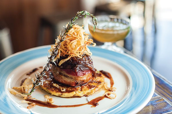 Bacon-wrapped bison meatloaf atop potato-cauliflower pancake, with fried onions, onion jam and balsamic onion jus