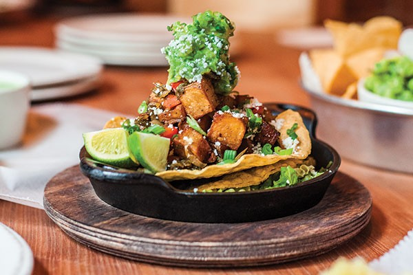 Papas: black beans, potatoes, poblano, queso fresco, guacamole, scallions shredded romaine and cilantro-buttermilk dressing