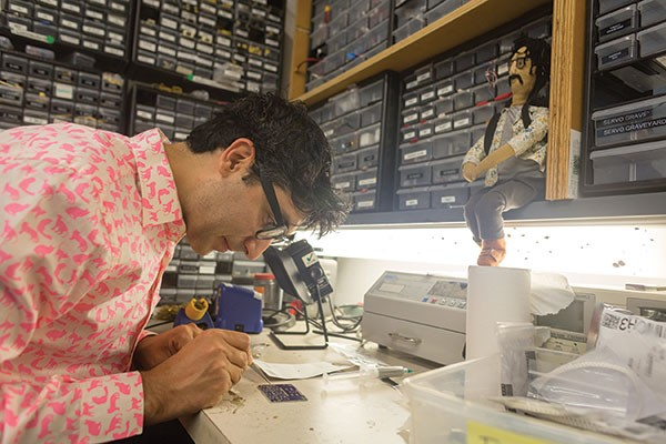 Ali Momeni solders a circuit-board at his lab at Carnegie Mellon University.