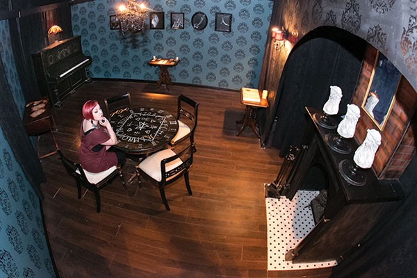 Macabre Noir, who art-directed the Imaginarium's Chamber of Illusions, sits in one of its mystery rooms.