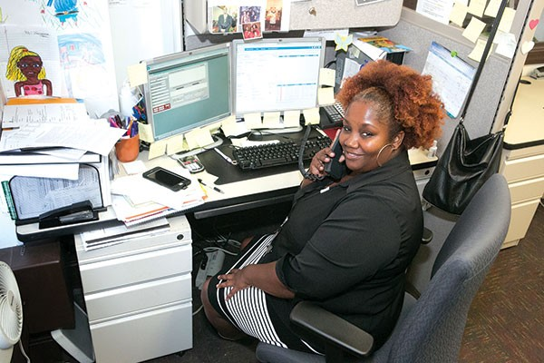 Ten-year 311 supervisor Naomi Johnson working at her desk