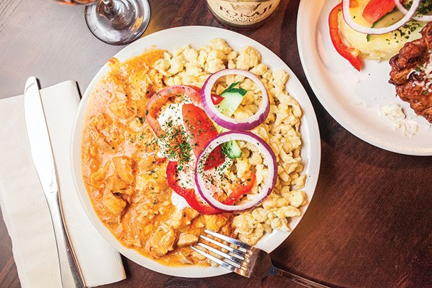 Stewed chicken paprikás, with sour-cream paprika, over nokedli