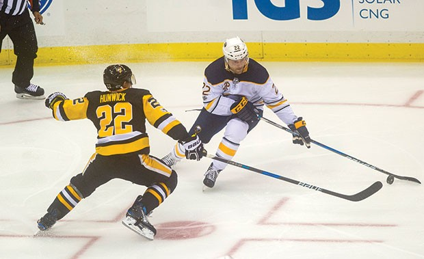 Matt Hunwick battles with Buffalo Sabres Johan Larsson on Sept. 27 at PPG Paints Arena. - CP PHOTO BY VINCENT PUGLIESE