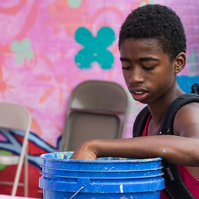 Kids work on a mural project in Homewood