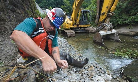 Workers install gabion baskets to prevent erosion along Girty's Run. - HEATHER MULL