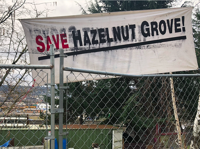 A banner hung over Hazelnut Groves fence, which the city plans on removing next month.