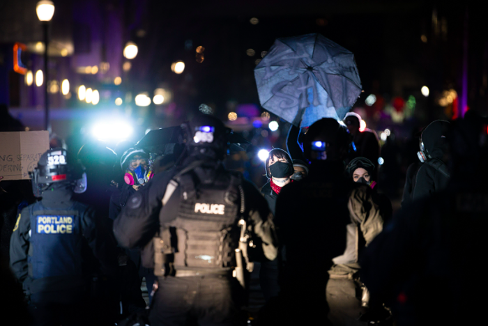 Portland police officers kettle a group of activists in the Pearl District Friday night.