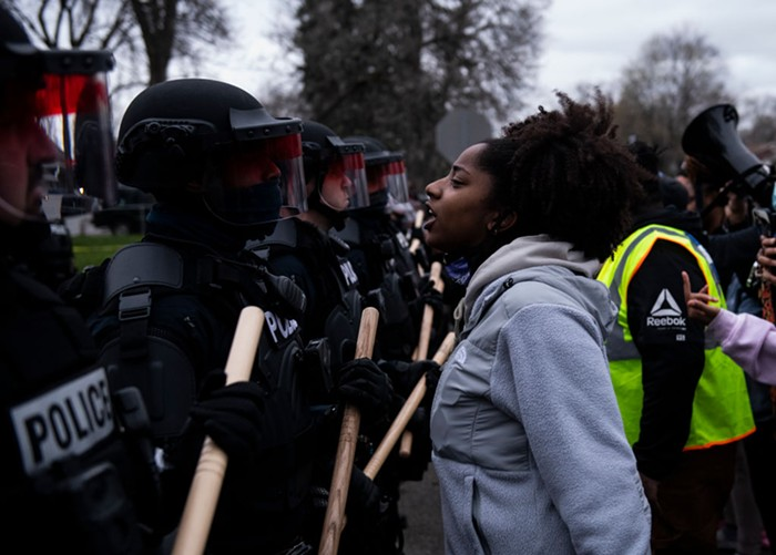 Protesters confront a line of riot police in Brooklyn Center, MN, who are blocking access to the scene where officers shot and killed Daunte Wright.