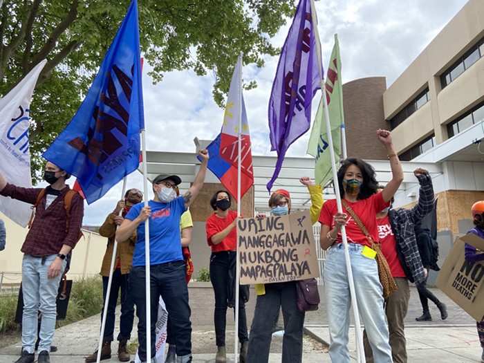 Members from Anakbayan, Migrante, and other migrant rights groups stand in front of the ICE building following a May Day march.