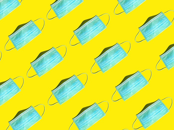 A repeating pattern of blue, disposable masks on a bright yellow background.