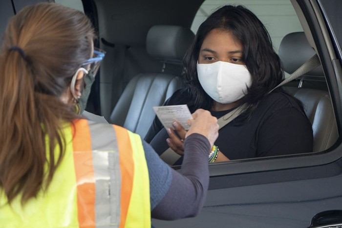 A Latinx person in a car, receiving their vaccination card from an OHSU health care provider.