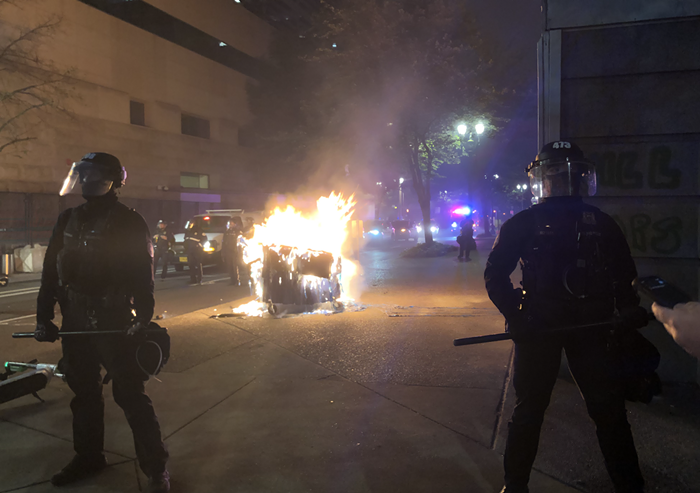 Portland police stand in front of a burning dumpster Tuesday night.