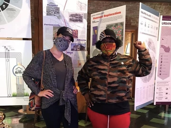 Two people in masks stand in front of large posters with designs, photos, and graphs. You can tell both people are smiling under their masks. One person has their first raise like the hand signal for Black Power.