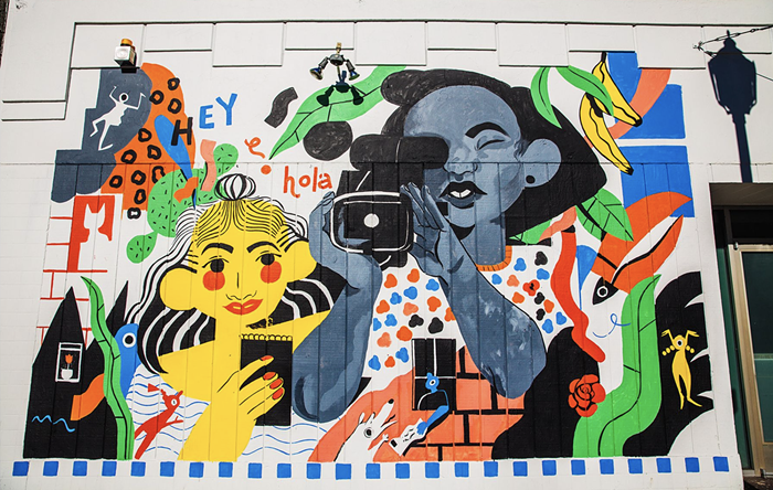 A colorful mural. Its abstract, but features a girl holding a video camera. There are english and Spanish words in the mural.