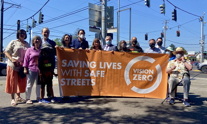 A group of people hold up an orange sign reading vision zero.