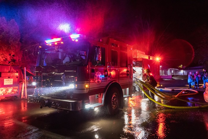A firetruck at night. A couple firemen surround the truck, working,