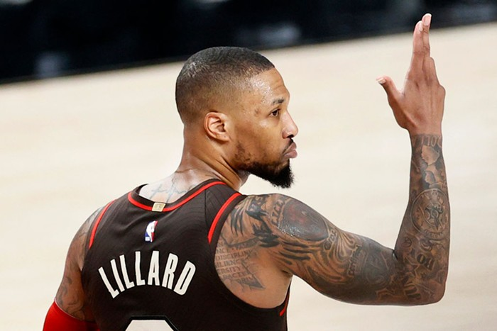 Damian Lillard during a basketball game. His back is to the camera and his arm is raised, celebrating a 3 pointer.