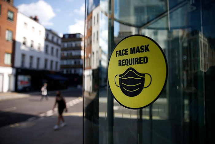 A yellow sign on a door reading face masks required