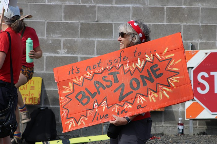 A person holds a sign reading its not safe to live in a blast zone