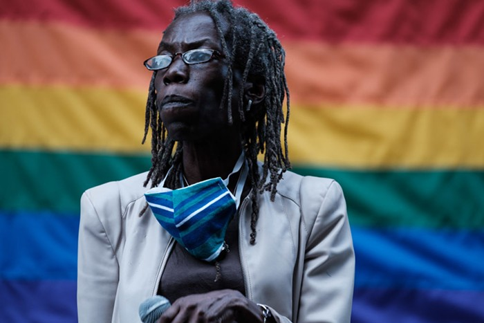 Jo Ann Hardesty stands in front of a rainbow flag with a microphone in her hand