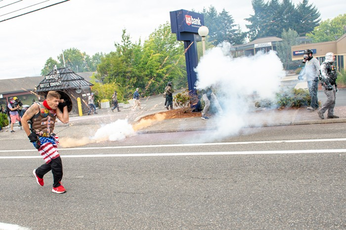 A man in American flag pants runs past an exploding firework