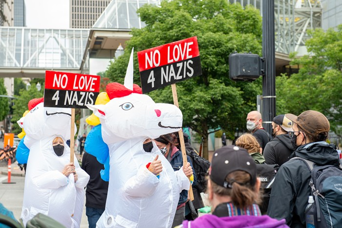 Two people in unicorn costumes holding anti-fascism signs
