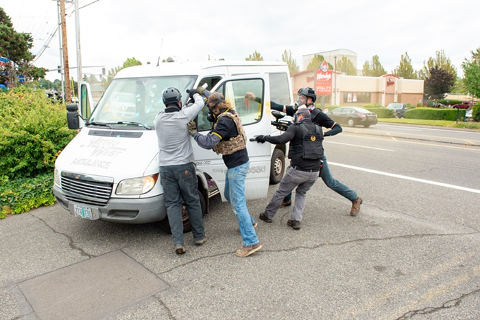 A group of people swarm a white van.
