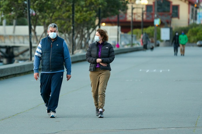 Two people walking outside with masks on