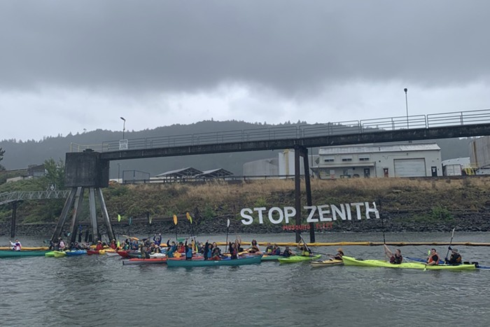 A group of 30 kayakers raise a banner reading stop zenith