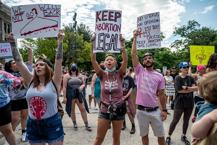 A group of protesters holding signs urging law makers to keep abortion legal