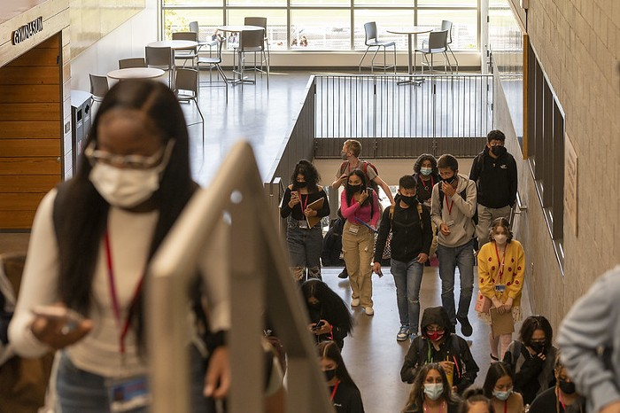 Masked high schoolers walk up the stairs in school. There is less than three feet between several students