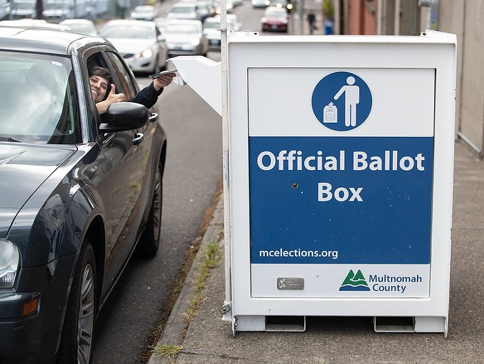 A person in their car reaching out the window to put their ballot in a ballot dropbox. They are looking at the camera and giving a thumbs up