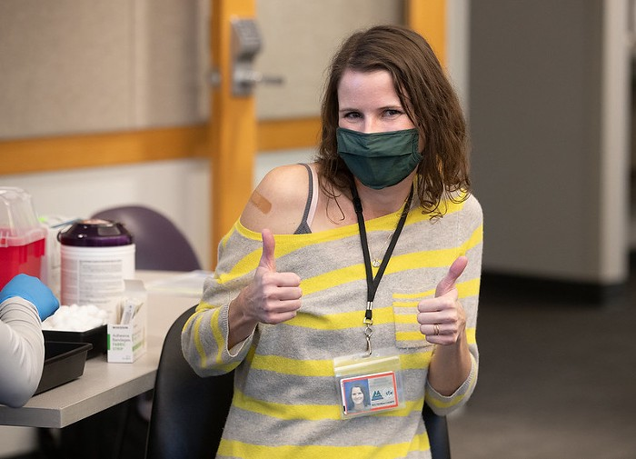 A person gives a thumbs up. Thy are wearign a mask and have a bandaid on their arm from where they just got the vaccine.
