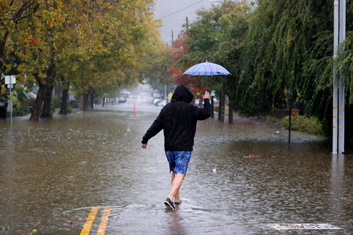 A person walks through flooding caused by the bomb cyclone in San Rafael, CA.
