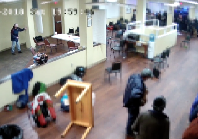 Elifritz stands in the top left corner of this video capture—hiding from police behind a pillar.