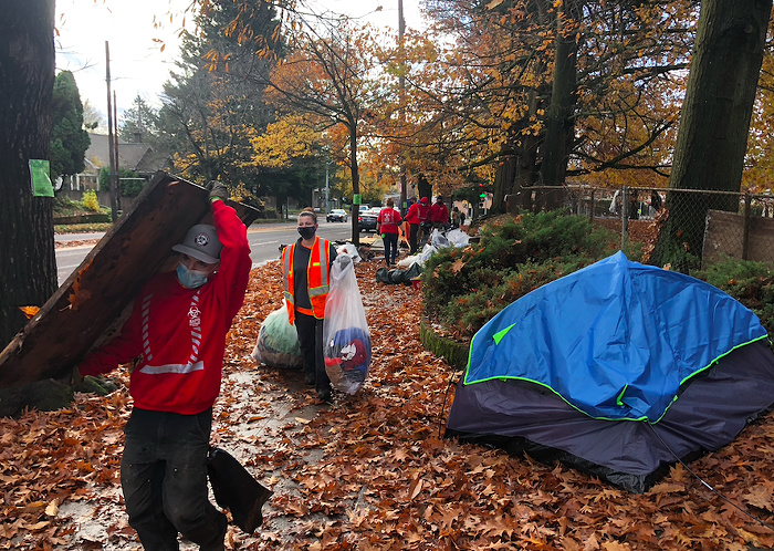 Staff contracted with HUCIRP remove trash and belongings from a SE Oak encampment alongside Laurelhurst Park in November.