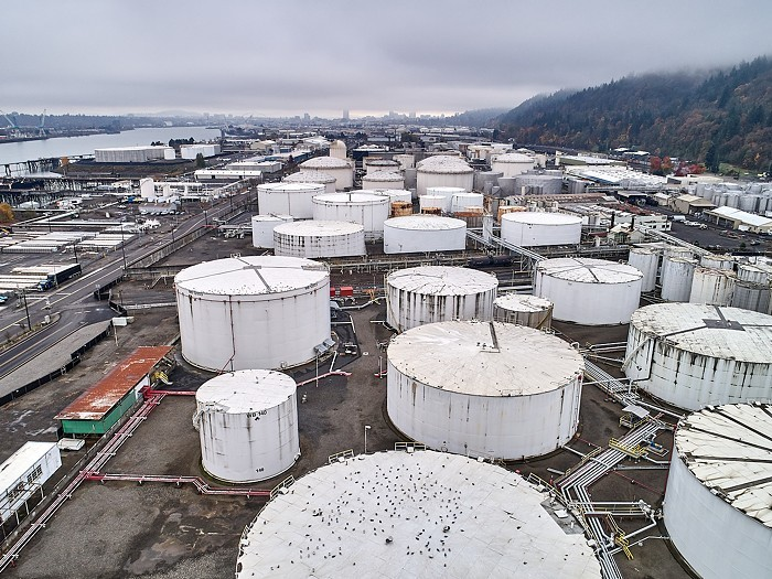 An overview of several white oil tanks clustered toegtehr. In the background you can see the Willamette River.
