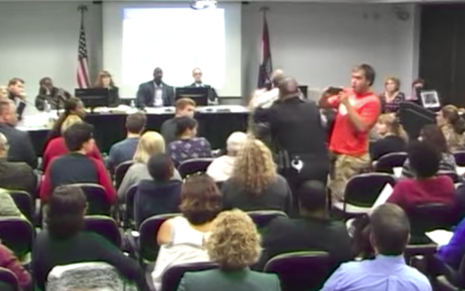 A man with a camera reacts as a St. Louis police officer knocks down Steve Taylor, an instructor attempting to speak at October 19's board of trustee meeting. - IMAGE VIA YOUTUBE