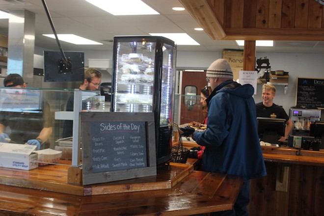 Customers enter a cafeteria-style line, with the day's sides on a chalkboard. - SARAH FENSKE