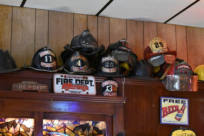Just some of the firefighter paraphernalia lining the bar's walls. - PHOTO BY DANIEL HILL