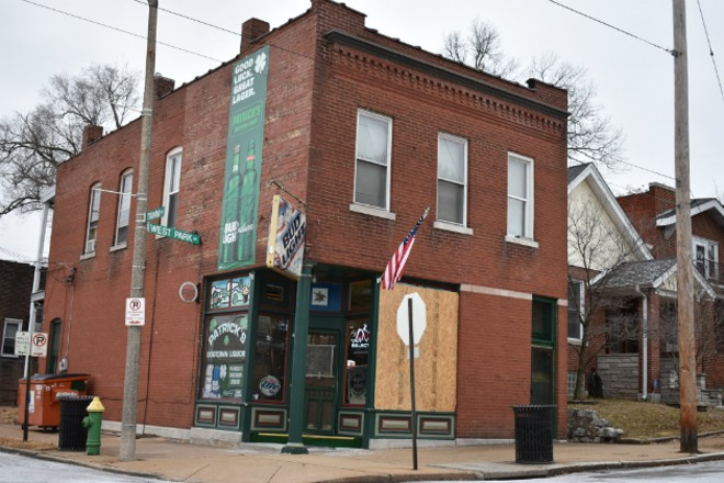 Patrick's Dogtown Liquor reopened with a boarded-up window after thieves shot out the glass. - PHOTO BY DOYLE MURPHY