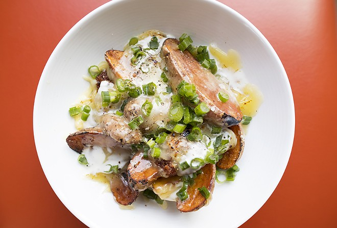 """New Town Skins"" are smothered in raclette cheese, spicy pork, green onion and housemade sour cream. - MABEL SUEN"