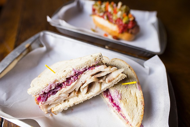 The pork belly sandwich, a riff on a Reuben, is topped with 1000 island dressing, braised cabbage and Swiss. - MABEL SUEN