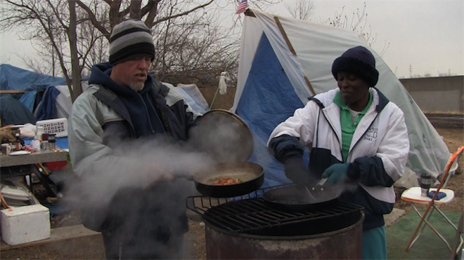 Sparta residents Bonnie and David cook over a fire. Crane shot this footage shortly after moving to the camp in 2011. - SCREEN SHOT FROM LIVING IN TENTS