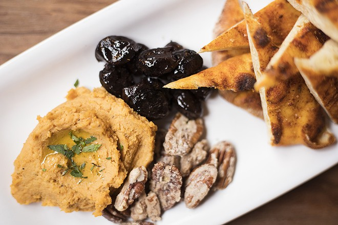 The spiced flatbread combines olives, candied pecans, honey, spicy hummus and preserved lemon. - MABEL SUEN