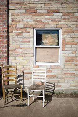 Chairs sit outside a broken window at the Garden Apartments. - SARA BANNOURA