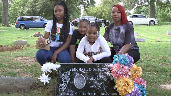 Michael Brown's family visits his resting place. - JASON POLLOCK